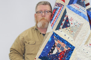 Mike Rudebusch with quilt of honor.